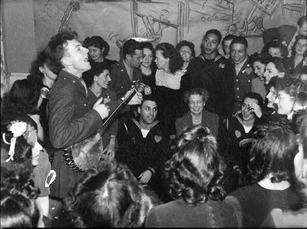 Pete Seeger entertaining Eleanor Roosevelt (center), honored guest at a racially integrated Valentine's Day party marking the opening of a Canteen of the United Federal Labor, CIO, in then-segregated Washington, D.C. Photographed by Joseph Horne for the Office of War Information, 1944.